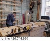 Мастер работает на производстве арф в арфовом цехе компании Resonance Harps в Санкт-Петербурге, фото № 26744930, снято 8 августа 2017 г. (c) Stockphoto / Фотобанк Лори