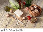 Купить «Feta cheese, mushrooms in a basket, olive oil in a jug and vegetables on a wooden table close-up», фото № 26747102, снято 18 марта 2017 г. (c) Татьяна Ляпи / Фотобанк Лори