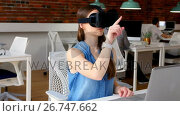 Купить «Female executive using virtual reality headset», видеоролик № 26747662, снято 10 декабря 2018 г. (c) Wavebreak Media / Фотобанк Лори
