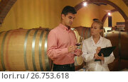 Купить «Professional sommelier advising male customer in winery cellar», видеоролик № 26753618, снято 1 октября 2016 г. (c) Яков Филимонов / Фотобанк Лори