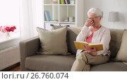 Купить «senior woman in glasses reading book at home», видеоролик № 26760074, снято 20 сентября 2019 г. (c) Syda Productions / Фотобанк Лори