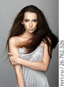 Beauty portrait of young woman. Brunette girl with long disheveled flying hair and day female makeup on gray background, фото № 26762326, снято 29 июня 2017 г. (c) Serg Zastavkin / Фотобанк Лори