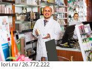 Купить «pharmacists standing with a cash desk», фото № 26772222, снято 23 ноября 2019 г. (c) Яков Филимонов / Фотобанк Лори