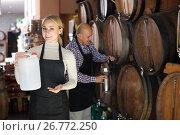 Купить «Glad mature man and young woman posing with wine from wood», фото № 26772250, снято 27 мая 2020 г. (c) Яков Филимонов / Фотобанк Лори