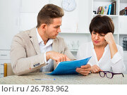 Man discusses correctness of paperwork with fellow worker. Стоковое фото, фотограф Яков Филимонов / Фотобанк Лори