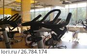 Купить «Bicycling simulators in the gym, interior of modern fitness club», видеоролик № 26784174, снято 27 апреля 2018 г. (c) Константин Шишкин / Фотобанк Лори