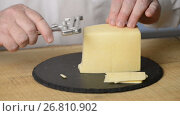 Купить «The man cuts cheese into thin slices with use of a cheese slicer on a black round chopping board from slate», видеоролик № 26810902, снято 23 июля 2017 г. (c) Anatoly Timofeev / Фотобанк Лори