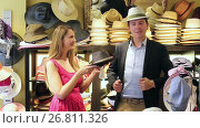 Купить «smiling adult woman and man trying on fashion hats in the shopping mall», видеоролик № 26811326, снято 16 мая 2017 г. (c) Яков Филимонов / Фотобанк Лори