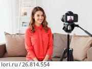 Купить «woman with camera recording video at home», фото № 26814554, снято 22 декабря 2016 г. (c) Syda Productions / Фотобанк Лори