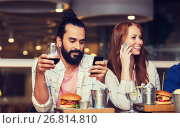 Купить «happy friends with smartphones at restaurant», фото № 26814810, снято 8 ноября 2015 г. (c) Syda Productions / Фотобанк Лори