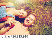 Купить «happy teenage couple lying on grass at summer», фото № 26815910, снято 19 июля 2016 г. (c) Syda Productions / Фотобанк Лори