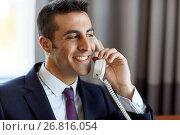 Купить «businessman calling on phone at hotel or office», фото № 26816054, снято 22 мая 2017 г. (c) Syda Productions / Фотобанк Лори