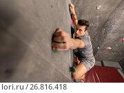 Купить «young man exercising at indoor climbing gym», фото № 26816418, снято 2 марта 2017 г. (c) Syda Productions / Фотобанк Лори