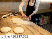 Купить «baker portioning dough with bench cutter at bakery», фото № 26817362, снято 15 мая 2017 г. (c) Syda Productions / Фотобанк Лори