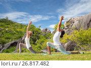 Купить «couple making yoga in low lunge pose outdoors», фото № 26817482, снято 6 августа 2014 г. (c) Syda Productions / Фотобанк Лори