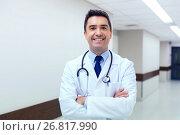 Купить «smiling doctor in white coat at hospital», фото № 26817990, снято 3 декабря 2015 г. (c) Syda Productions / Фотобанк Лори