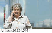 Купить «Mature old woman talks using smart phone outdoors», видеоролик № 26831546, снято 14 августа 2017 г. (c) worker / Фотобанк Лори