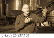 Купить «Worker of winery costs with glass of red wine near tanks», фото № 26837150, снято 12 октября 2016 г. (c) Яков Филимонов / Фотобанк Лори