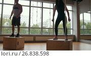 Купить «Sporty woman and muscular man fitness instructor doing box jump exercise during a workout at the gym», видеоролик № 26838598, снято 20 апреля 2018 г. (c) Константин Шишкин / Фотобанк Лори