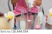 Купить «people with drinks eating food at outdoor table», видеоролик № 26844554, снято 17 июля 2019 г. (c) Syda Productions / Фотобанк Лори