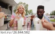 Купить «friends with food clinking drinks at outdoor table», видеоролик № 26844582, снято 15 октября 2019 г. (c) Syda Productions / Фотобанк Лори