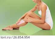 Купить «woman removing leg hair with depilatory wax strip», фото № 26854954, снято 9 апреля 2017 г. (c) Syda Productions / Фотобанк Лори