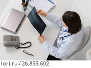 Купить «doctor with spine x-ray sitting at table», фото № 26855602, снято 4 апреля 2017 г. (c) Syda Productions / Фотобанк Лори