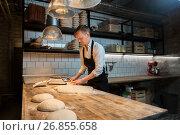 Купить «baker portioning dough with bench cutter at bakery», фото № 26855658, снято 15 мая 2017 г. (c) Syda Productions / Фотобанк Лори