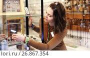 Купить «Young girl buyer looking of colored necklaces and pendants in the store», видеоролик № 26867354, снято 2 мая 2017 г. (c) Яков Филимонов / Фотобанк Лори