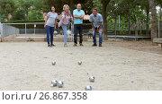 Купить «Cheerful males and females playing petanque in th park on holidays», видеоролик № 26867358, снято 28 июля 2017 г. (c) Яков Филимонов / Фотобанк Лори