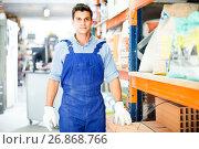 Купить «Portrait of diligent male in uniform on his workplace in building store.», фото № 26868766, снято 26 июля 2017 г. (c) Яков Филимонов / Фотобанк Лори