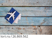 airplane on a passport with air tickets, close-up, on a wooden background. Стоковое фото, фотограф Tetiana Chugunova / Фотобанк Лори
