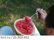 Купить «A young man is eating a watermelon with a spoon. The concept of healthy nutrition and vegetarianism», фото № 26869602, снято 21 августа 2017 г. (c) Tetiana Chugunova / Фотобанк Лори