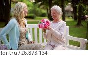 Купить «daughter with flowers and gift for senior mother», видеоролик № 26873134, снято 19 июля 2019 г. (c) Syda Productions / Фотобанк Лори