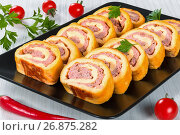 Купить «Cheese meat roll-ups on black rectangular dish, close-up», фото № 26875282, снято 18 февраля 2019 г. (c) Oksana Zh / Фотобанк Лори
