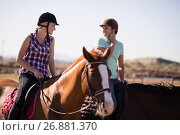 Купить «Happy female friends talking while horseback riding», фото № 26881370, снято 3 мая 2017 г. (c) Wavebreak Media / Фотобанк Лори