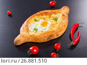 Купить «khachapuri with egg on black background, view from above», фото № 26881510, снято 15 сентября 2019 г. (c) Oksana Zh / Фотобанк Лори