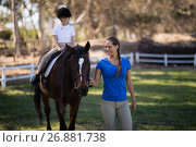 Купить «Smiling female jockey holding bridle while sister sitting on horse», фото № 26881738, снято 3 мая 2017 г. (c) Wavebreak Media / Фотобанк Лори