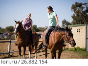 Купить «Female friends talking while sitting on horse», фото № 26882154, снято 3 мая 2017 г. (c) Wavebreak Media / Фотобанк Лори
