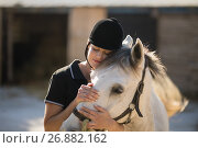 Купить «Female jockey embracing horse at barn», фото № 26882162, снято 3 мая 2017 г. (c) Wavebreak Media / Фотобанк Лори