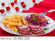 Купить «sliced smoked veal fillet, french fries and red cabbage salad with carrots cut into strips and parsley dressing with vinegar and olive oil on table mat with cherry tomatoes on white rustic boards, close-up», фото № 26882226, снято 19 декабря 2018 г. (c) Oksana Zh / Фотобанк Лори