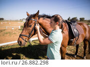 Купить «Side view of female jockey fastening bridle», фото № 26882298, снято 3 мая 2017 г. (c) Wavebreak Media / Фотобанк Лори