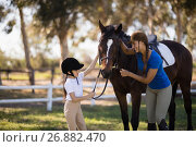 Купить «Happy girl and female jockey stroking horse», фото № 26882470, снято 3 мая 2017 г. (c) Wavebreak Media / Фотобанк Лори