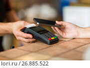 Купить «hands with payment terminal and smartphone at bar», фото № 26885522, снято 8 декабря 2016 г. (c) Syda Productions / Фотобанк Лори