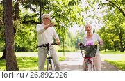 happy senior couple riding bicycles at summer park. Стоковое видео, видеограф Syda Productions / Фотобанк Лори