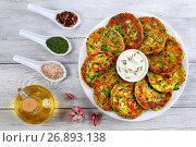 Купить «delicious zucchini fritters on white plate with sour cream in centre of dish sprinkled with finely chopped chives, spices. bottle of olive oil on wooden table, vegetarian recipe, view from above», фото № 26893138, снято 21 июля 2017 г. (c) Oksana Zh / Фотобанк Лори