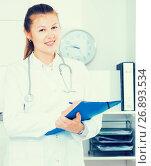 Купить «Doctor girl is signing patient`s diagnosis», фото № 26893534, снято 24 мая 2019 г. (c) Яков Филимонов / Фотобанк Лори