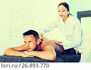Купить «female masseur doing massage at back man who lying on a massage table in a beauty salon», фото № 26893770, снято 12 июня 2017 г. (c) Яков Филимонов / Фотобанк Лори