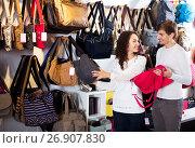 Купить «Female shopgirl helping young man to select handbag», фото № 26907830, снято 16 октября 2018 г. (c) Яков Филимонов / Фотобанк Лори