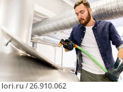 Купить «man with hose working at craft beer brewery kettle», фото № 26910062, снято 24 марта 2017 г. (c) Syda Productions / Фотобанк Лори